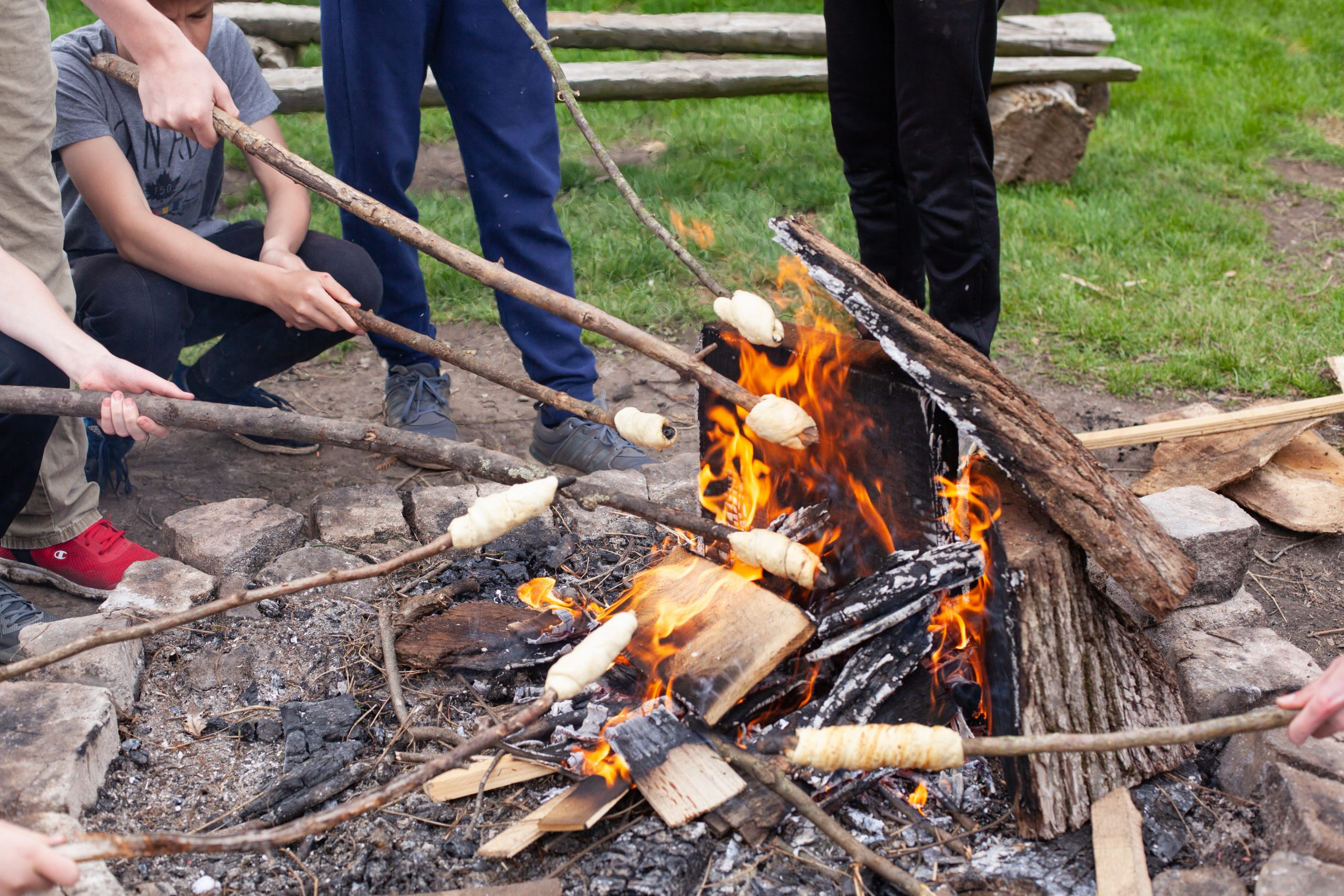 Campers standing around a campfire roasting marshmallows on the end of a stick at summer camp.