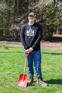 A staff member named Ari holding a red shovel, smiling, standing on a grass field.
