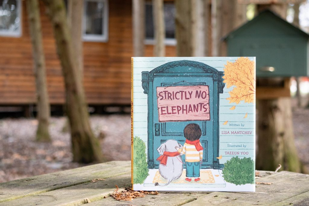 """The book """"Strictly No Elephants"""" propped upright on a picnic table in front of a cabin at summer camp."""