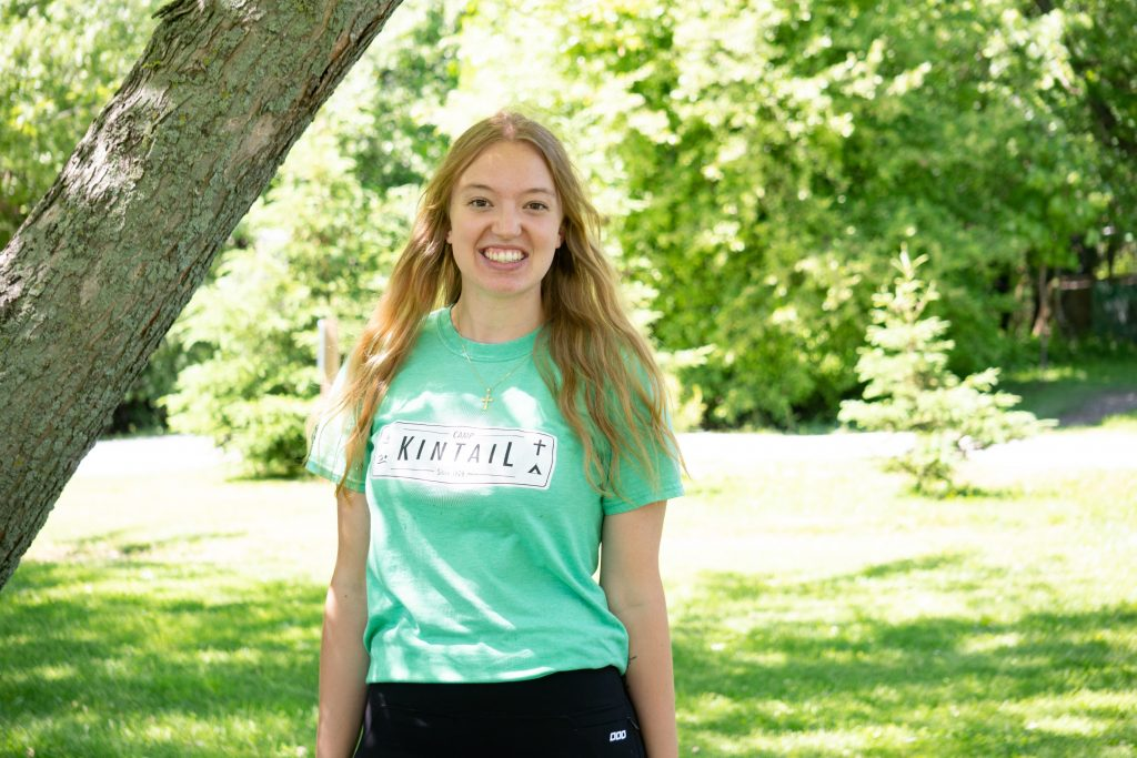 A camp kintail staff member named Piglet stands smiling by a tree wearing her bright green Camp Kintail staff t-shirt.