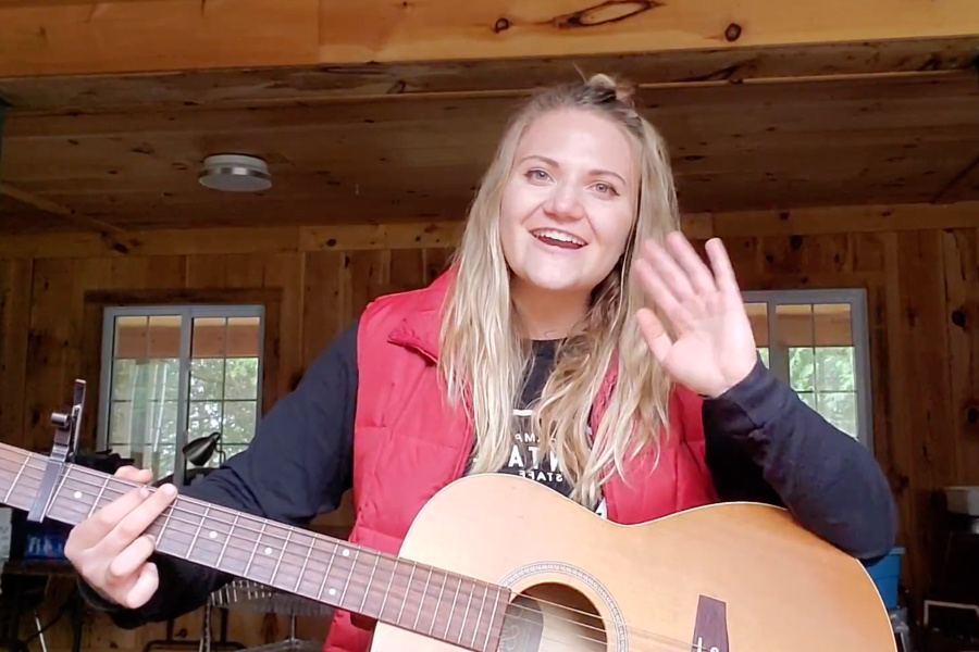 A camp staff member named Beebalm waves at the camera smiling with her guitar in her lap.