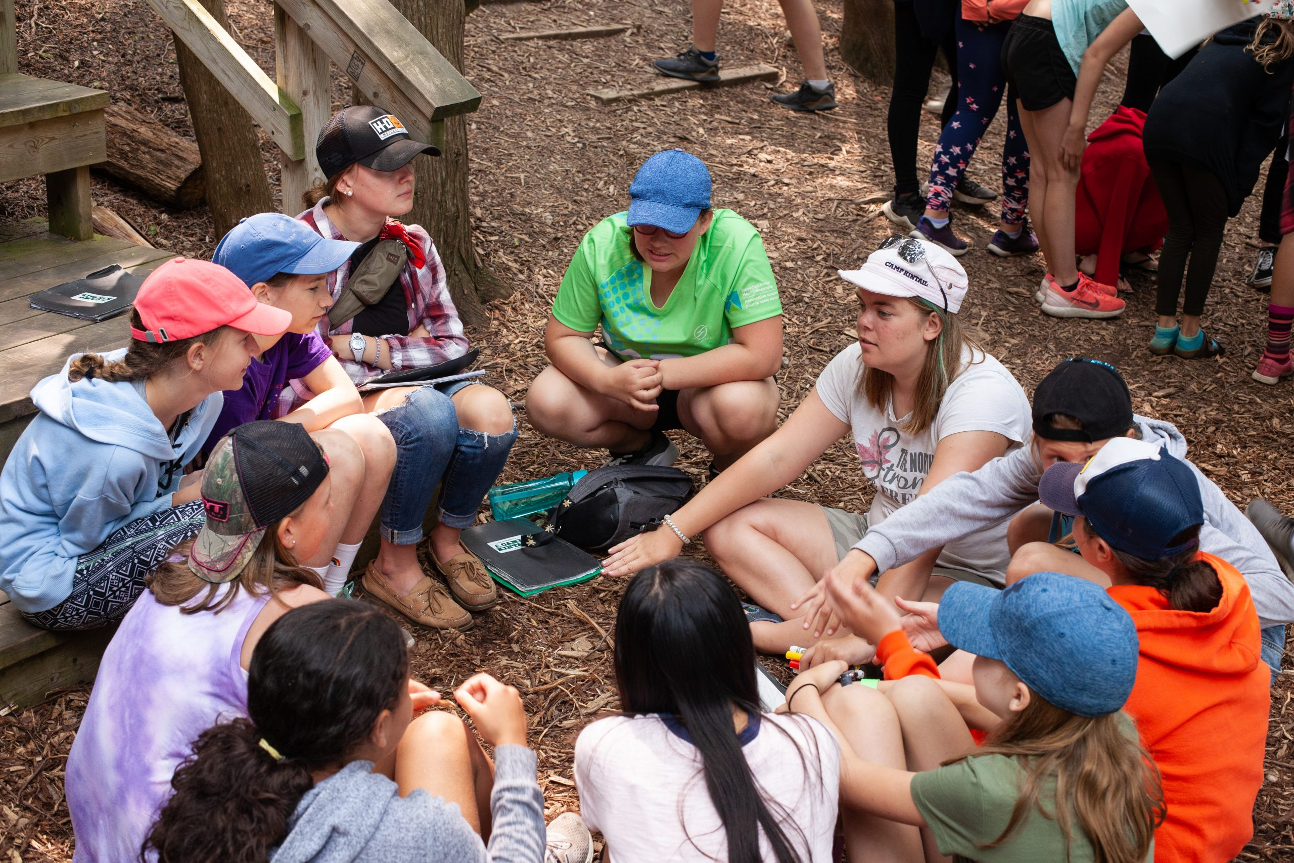 A cabin of campers with their counsellor sit in the Outdoor Chapel on the mulch in a circle talking.