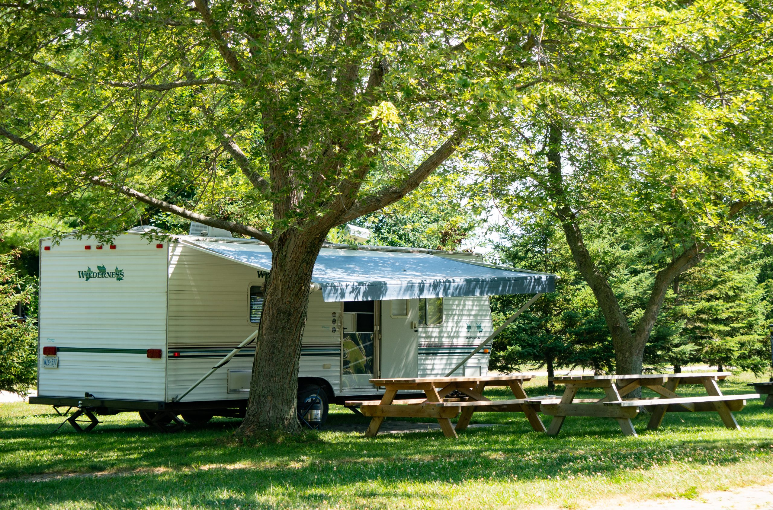 A camper trailer set up amongst trees on a grassy field with picnic tables in front.