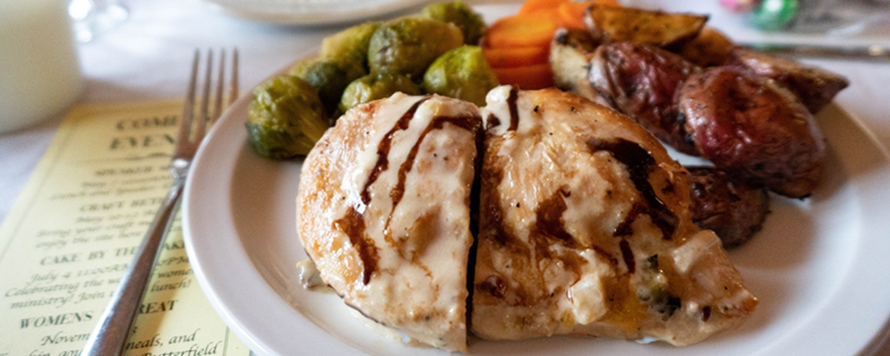 Stuffed balsamic chicken with brussel sprouts, carrots, and roasted potatoes on a dinner plate.