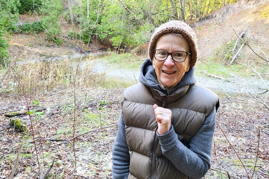 An older women stands smiling down by Kerry's Creek.