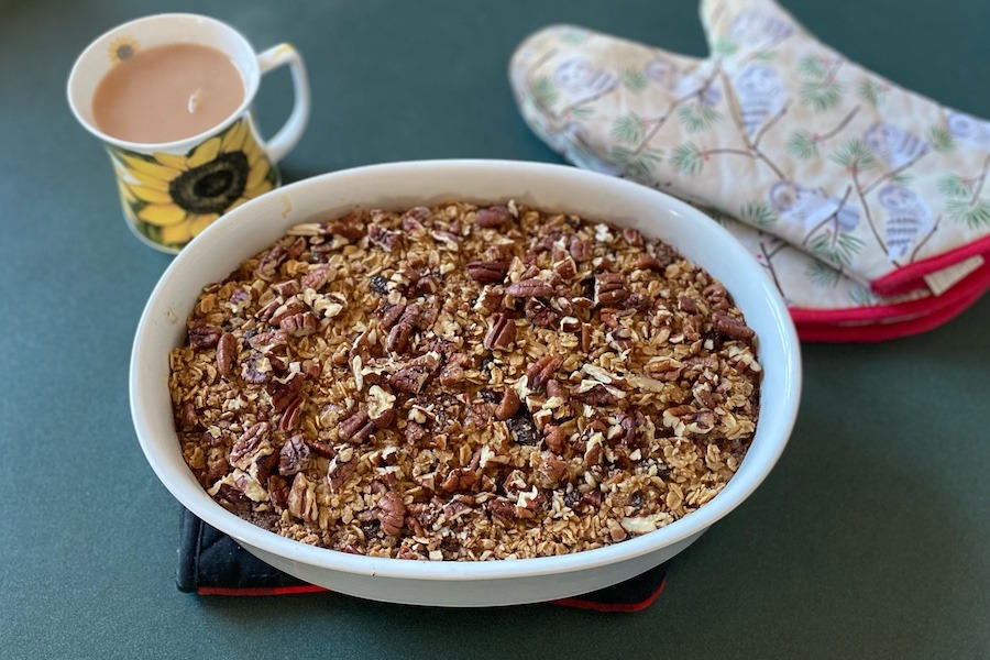 An oatmeal bake in a bowl with a mug of coffee and oven mitts beside it.