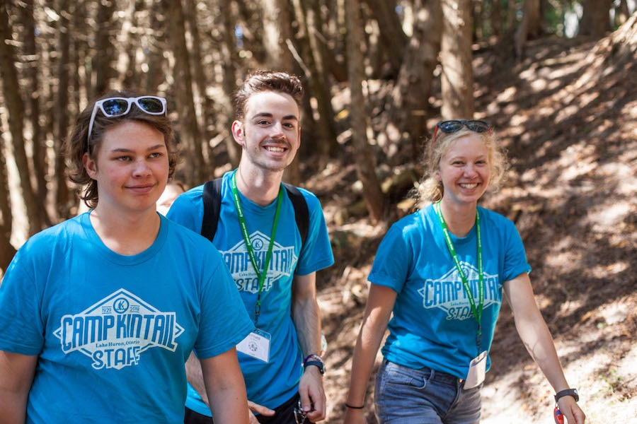 Three staff members wearing blue Camp Kintail t-shirts are smiling and walking along cedar tree shaded pathway at summer camp.