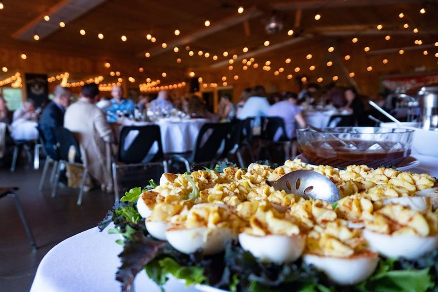 Devilled eggs sitting on lettuce on a tray on a table dressed with a white tablecloth in MacDonald Lodge. Edison lights and various wedding guests sitting at tables can be seen in the background.