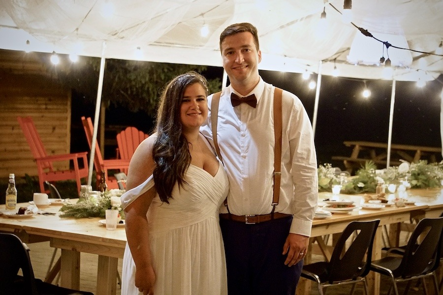 A bride and groom with their arms wrapped around one another's waist smile at the camera. It is the evening and they are standing underneath an outdoor white tent that is light up with Edison lights.