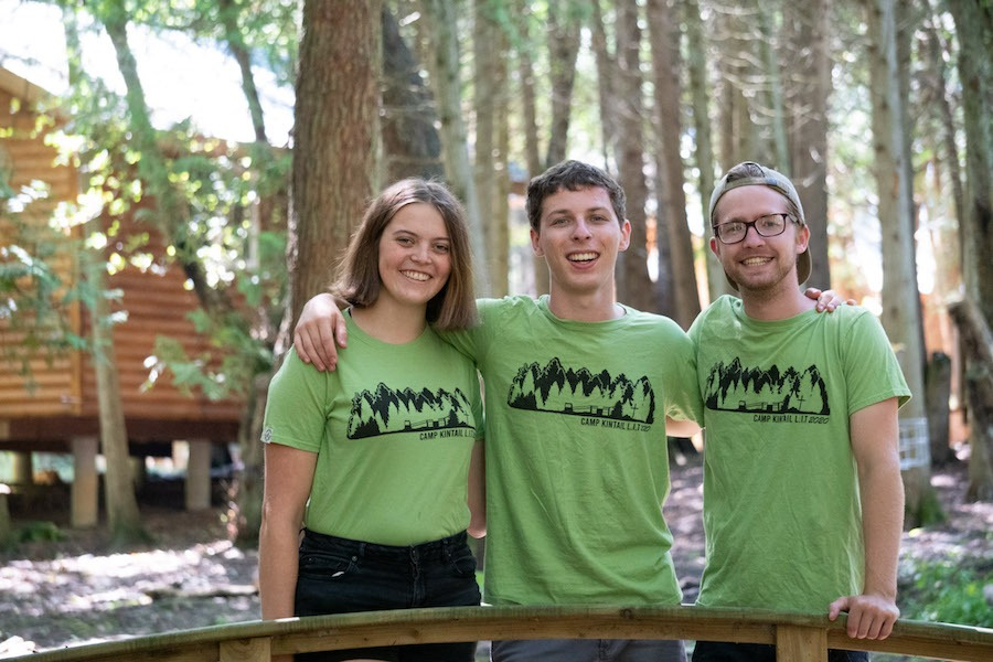 Three staff members named Columba, Sound, and Digit stand on a small bridge amongst cedar trees with their arms around each other smiling.