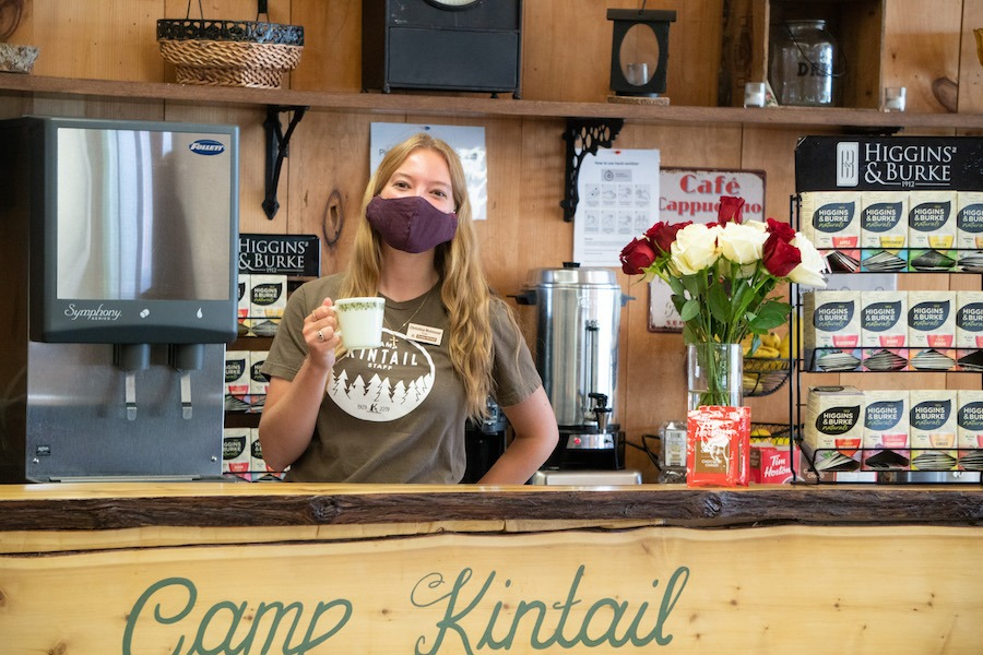 Staff member named Piget creates a welcoming gesture holding a coffee mug at the hospitality counter and is masked.