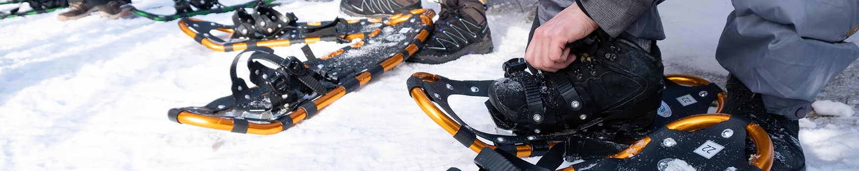 Participants feet are shown while they put on snowshoes during winter camp. They are located outdoors with snow covering the ground beneath them.
