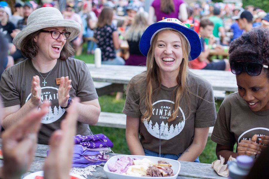 A camp staff named Piglet is wearing a birthday hat and smiling while seated at a picnic table while staff and campers around her clap, smile, and sing happy birthday at summer camp.