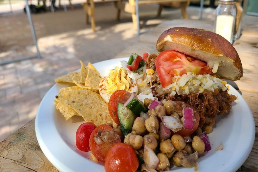Pulled pork on a bun with a chickpea salad and taco chips is on a plate on a picnic table.