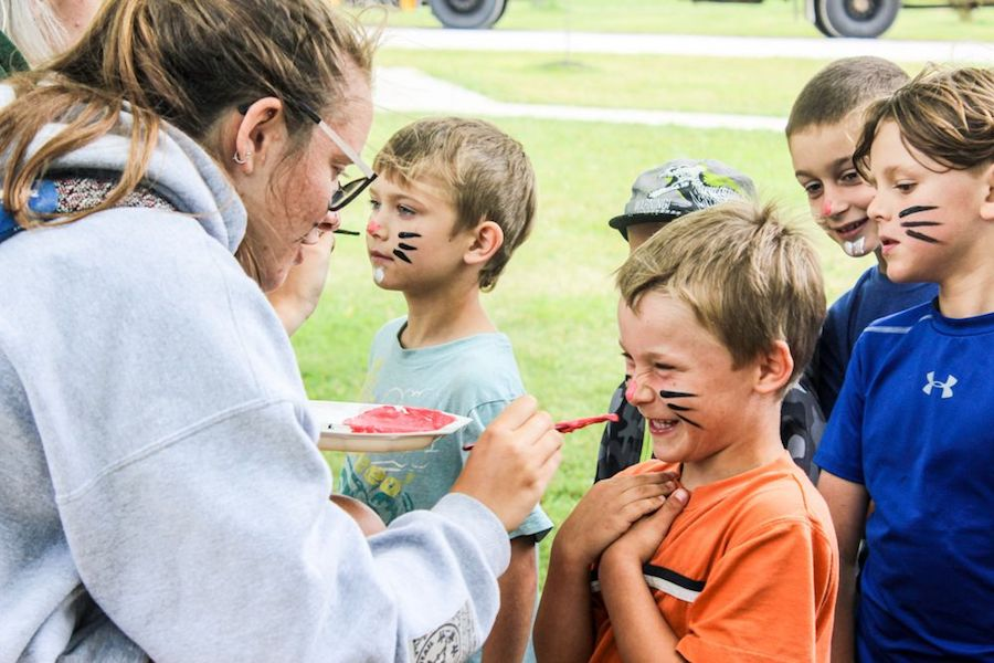 A staff member named Lobster is painting bunny whiskers on young campers' faces. The campers are smiling and laughing.