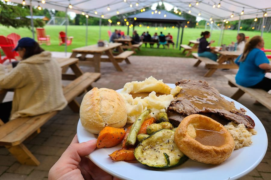 Roast beef, mashed potatoes, grilled vegetables, white bread roll, and yorkshire pudding with gravy on a white dinner plate behind held under the white, outdoor tent on the patio at MacDonald Lodge.