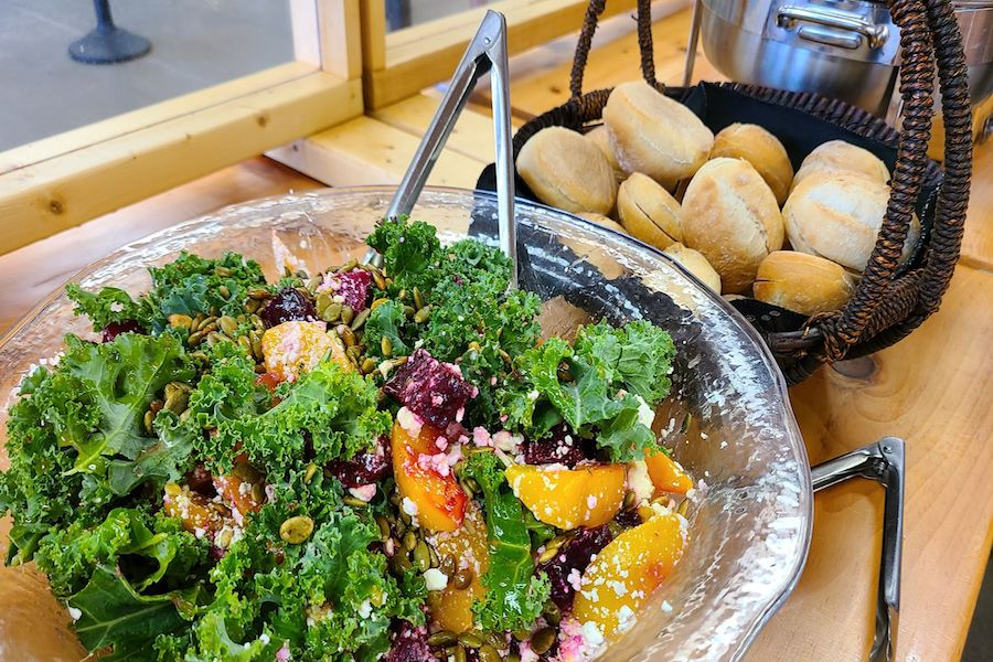 Fresh kale salad from the summer camp garden is prepared in a bowl. A basket of bread is set next to it.