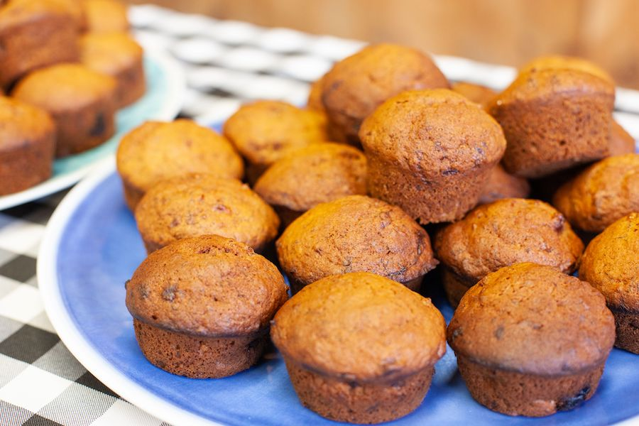 Fresh muffins are on a tray on the kitchen counter.