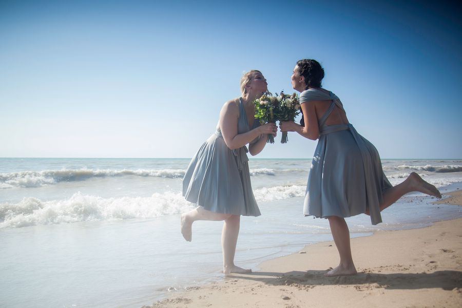 Two bridesmaids wearing pale blue dresses look at one another, smiling, and balancing on one foot with the other kicked out behind them, on the sandy shores of Lake Huron.