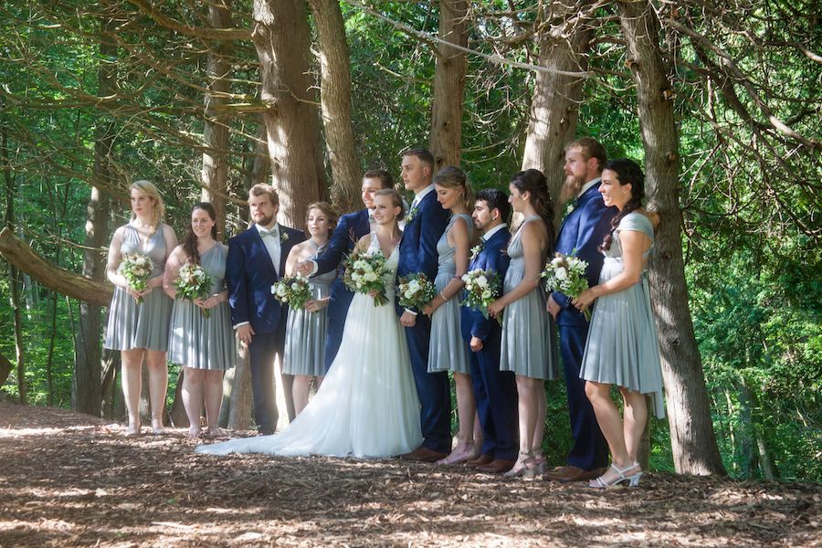 A wedding couple and their wedding party are in a line, smiling, on the canoe path in the cedar forest at summer camp.