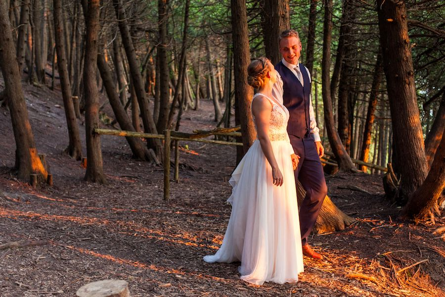 A bride and groom look into each other's eyes smiling in the Outdoor Chapel at summer camp.
