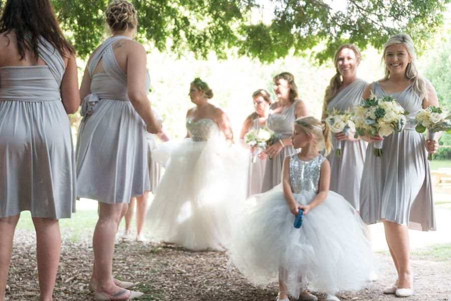 A bride with her six bridesmaids and flower girl are shaded under a tree. They are looking at one another smiling and the four bridesmaids to the right are each holding a small bouquet of white flowers.