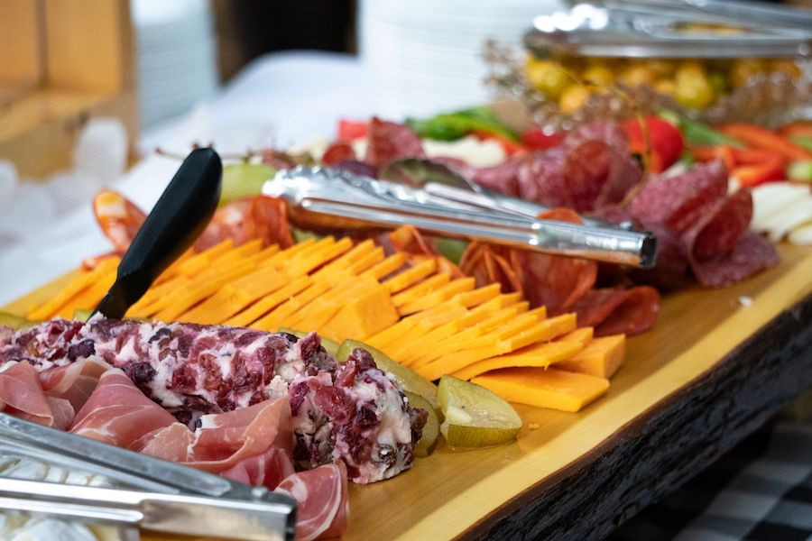 Charcuterie board made up of meats and cheeses in on a wooden tray on the buffet.