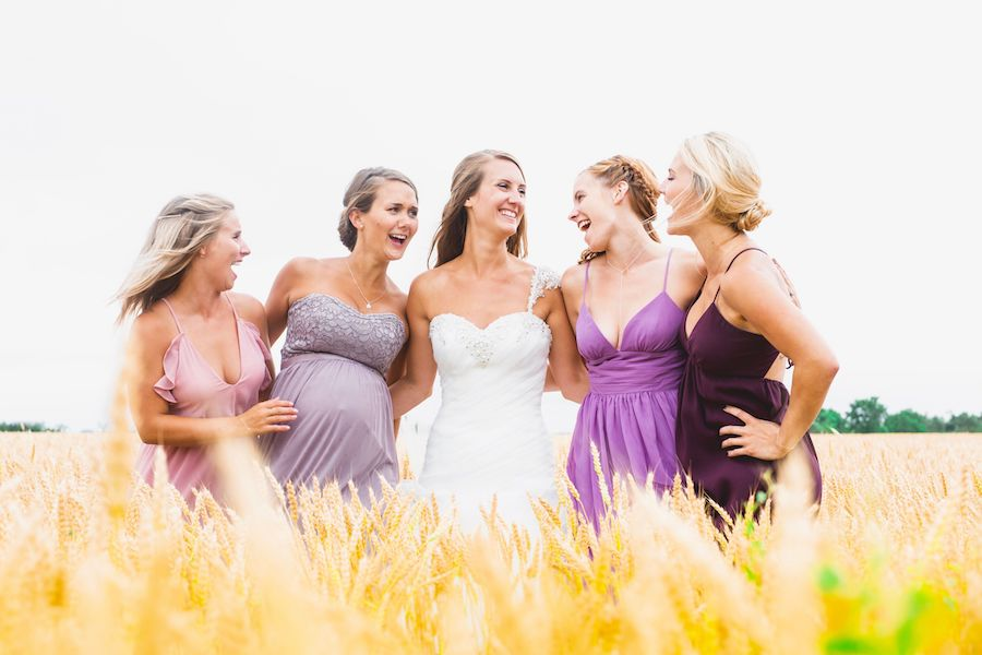 A bride along with four bridesmaid's who are wearing different purple hue dresses are looking at one another, smiling, in a wheat field.