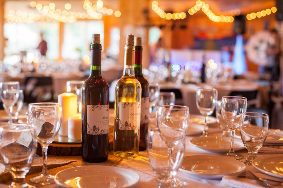 Glassware along with a bottle of red and white wine is illuminated on a wedding table that is dressed with white linens from the Edison lights hanging overhead.