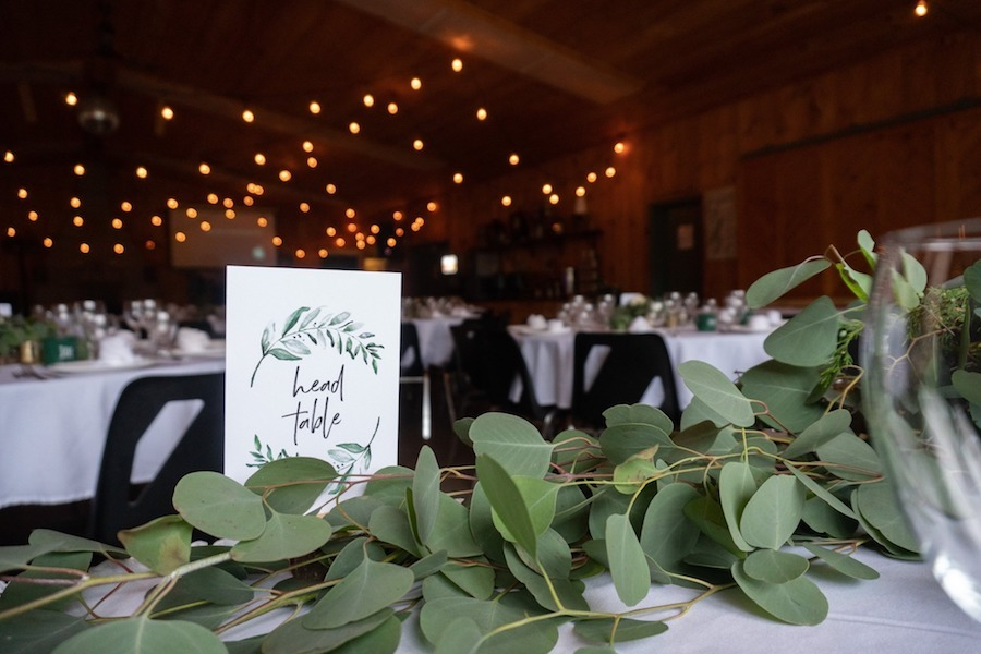 A scenic close up view of the head table at a summer camp wedding. There are evergreen leafs decorating the table that are illuminated from the Edison lights overhead at MacDonald Lodge.