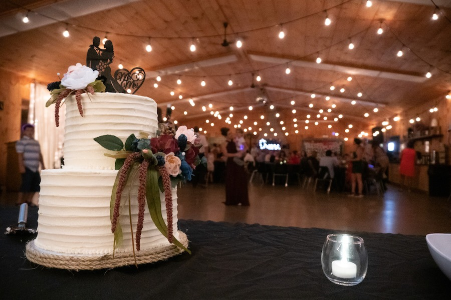 A white wedding cake with flowers on the second and top tier as decor is on a table with a black tablecloth. Behind you can see wedding guests mingling with the Edison lights on overhead at the MacDonald Lodge dining hall.