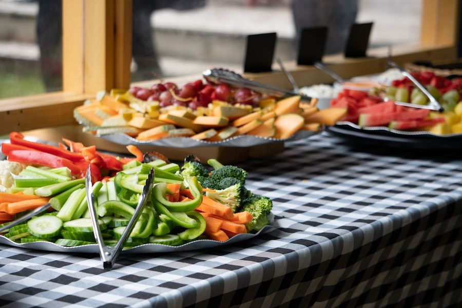 Fruit and vegetable platters along with cheese and cracker platters are on trays on a buffet.