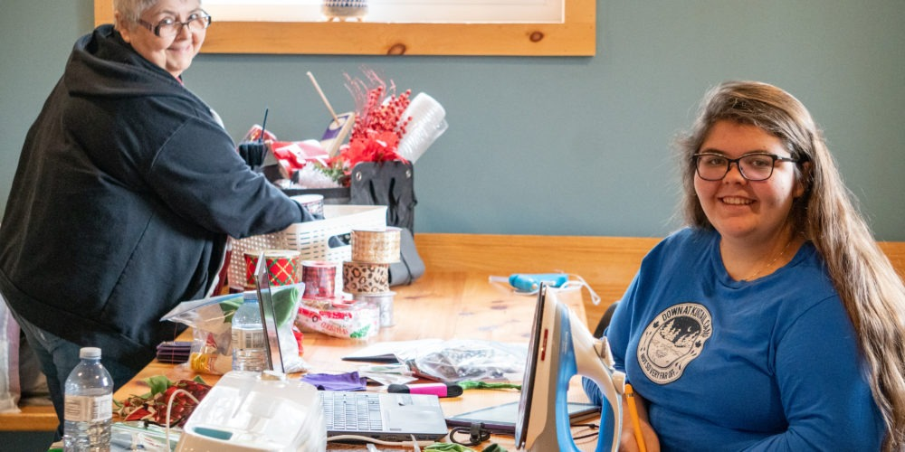 Staff member named Tora and her mother sit at a pine harvest table in the Nest Basement working on craft projects at Camp Kintail.