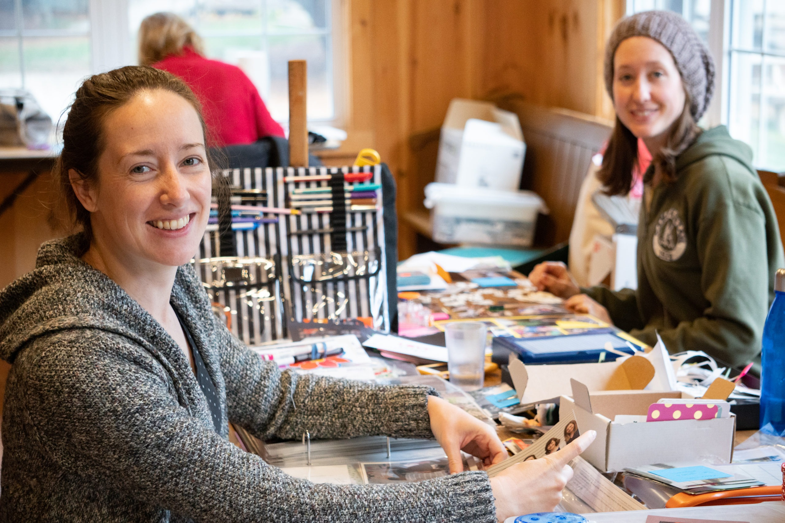 Three participants are smiling at the camera while sitting at their crafting table for Camp Kintail's Craft Retreat.