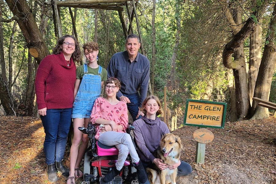 The MacDonald-Lee family from left to right, Theresa, Anna, Lucy, Johnathon, and Ella pose smiling.