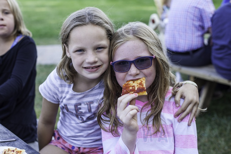 Two campers sit next to one another on a picnic table at summer camp. One has their arm wrapped around the other, while the second camper is eating a slice of pizza.
