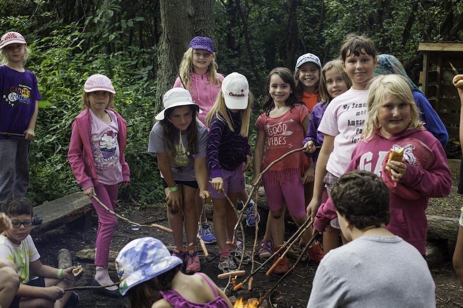 A group of campers stand around a campfire roasting hot dogs at summer camp.