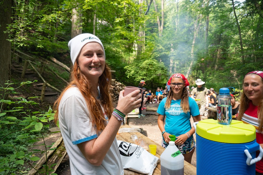 Staff members are smiling around a harvest table with lunch supplies at a campfire cookout during Outdoor Adventure Camp.