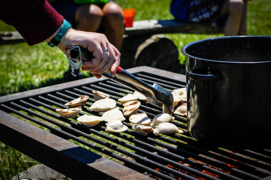 Perogies are cooked on a metal grate over a campfire.
