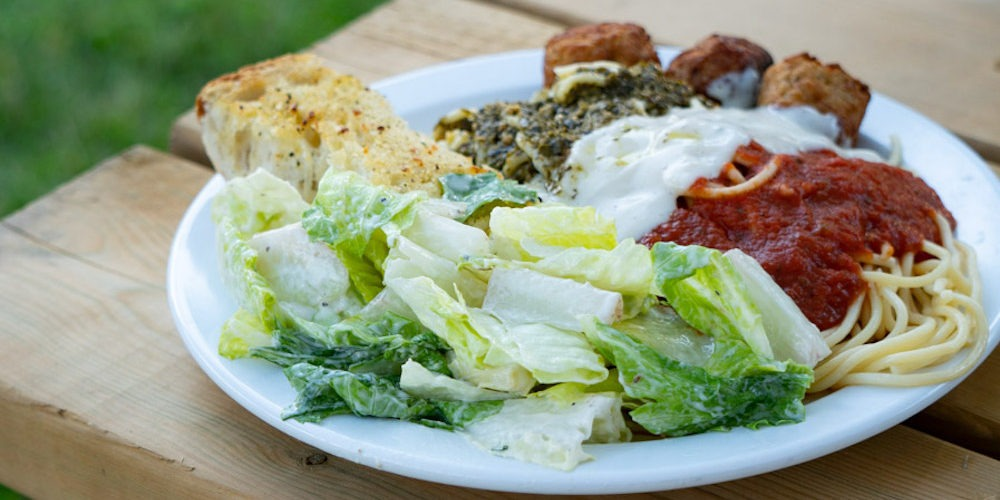 A plate made up with Caesar salad, garlic bread, and spaghetti with pesto, Alfredo, and red sauce with meatballs.
