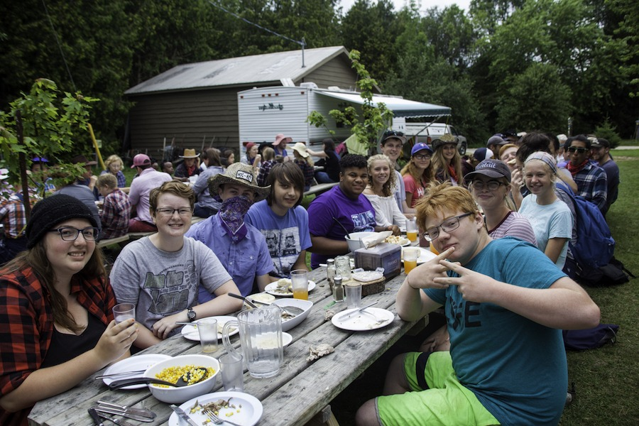 A group of Leader In Training campers at summer camp are seated at a picnic table smiling having just finished their meal.