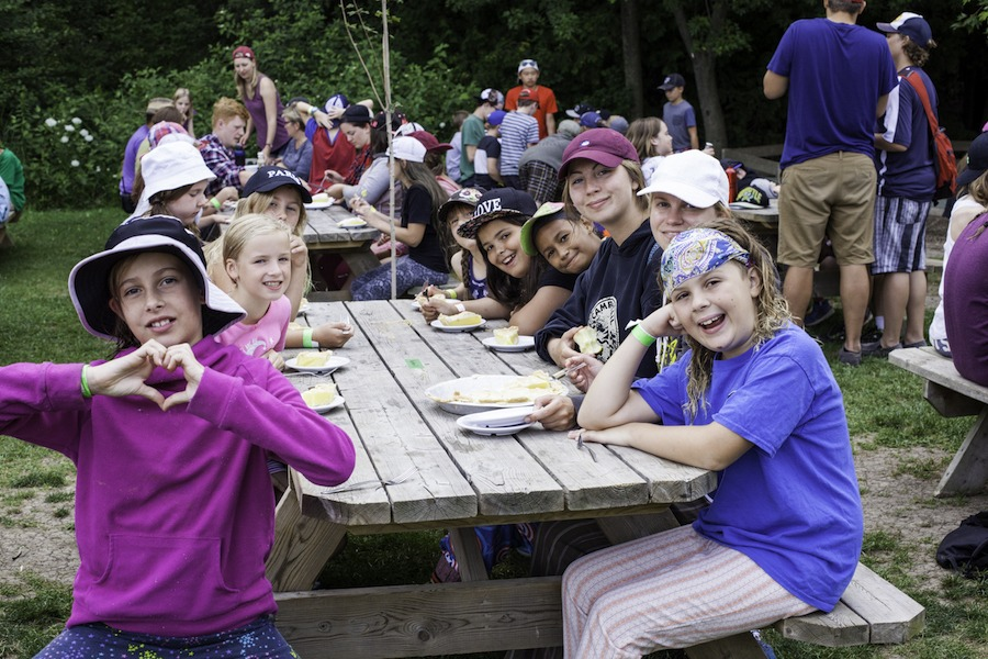 A group of campers are seating at a picnic table smiling, enjoying their meal at summer camp.