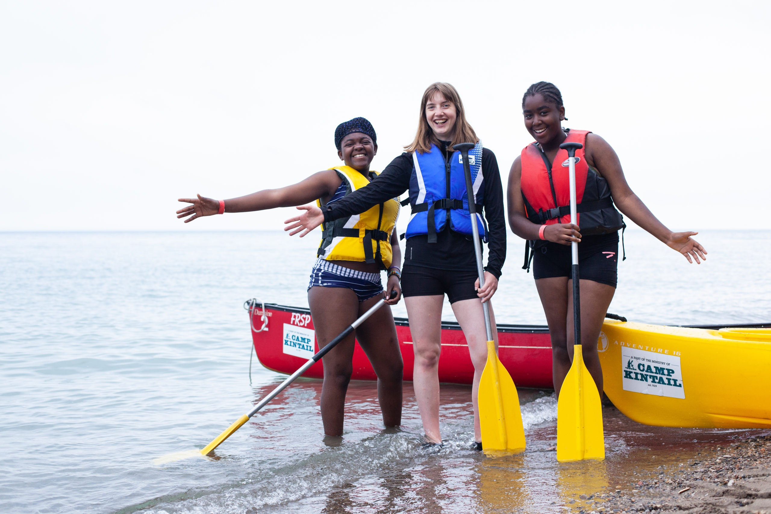 A staff member named Calaman stands between two campers in the shallow waters just off the shore of Lake Huron. They are each holding a paddle with a canoe in behind them.
