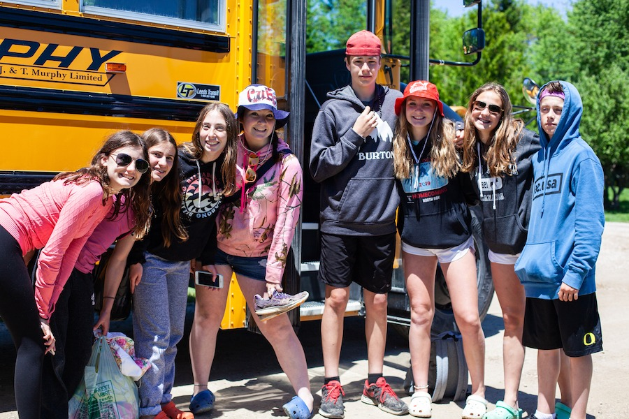 A group of eight students pose smiling in front of a school bus at summer camp.