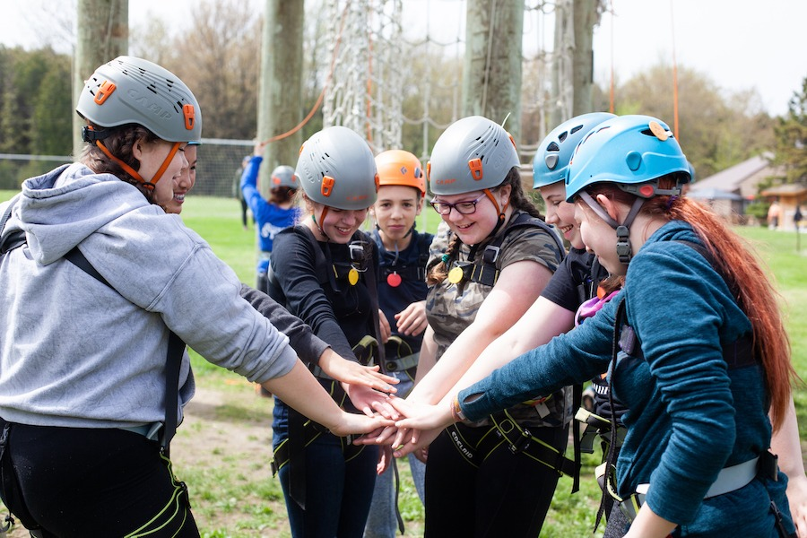 A staff member named Jabiru and five campers all wearing harnesses and helmets at the high ropes challenge course huddle up, placing their hands together in the centre of the circle.