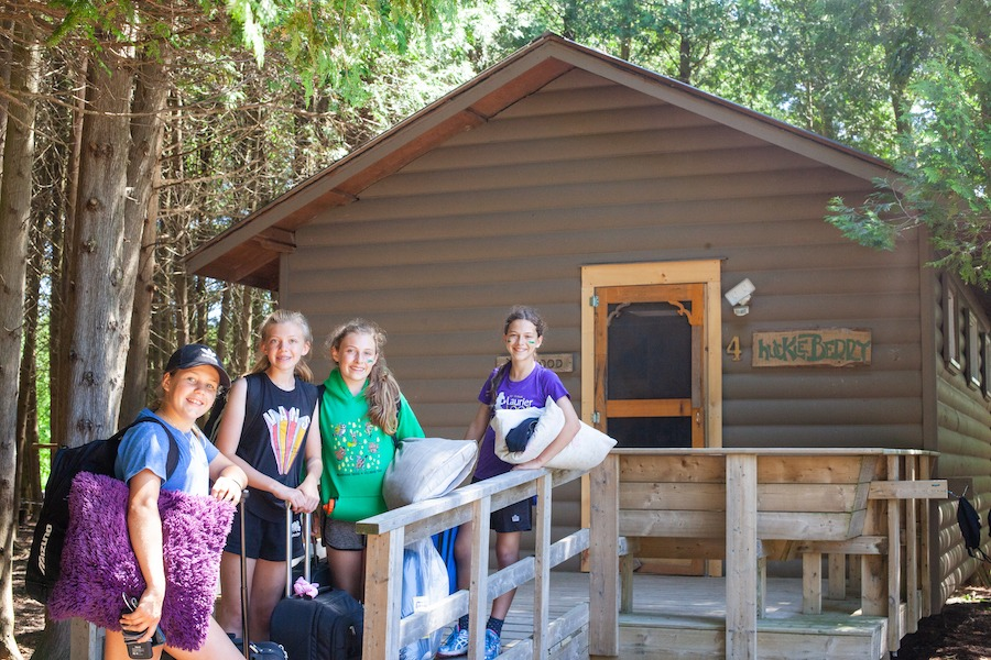 Four campers are smiling on a cabin deck with suitcases and pillows, ready for overnight summer camp!