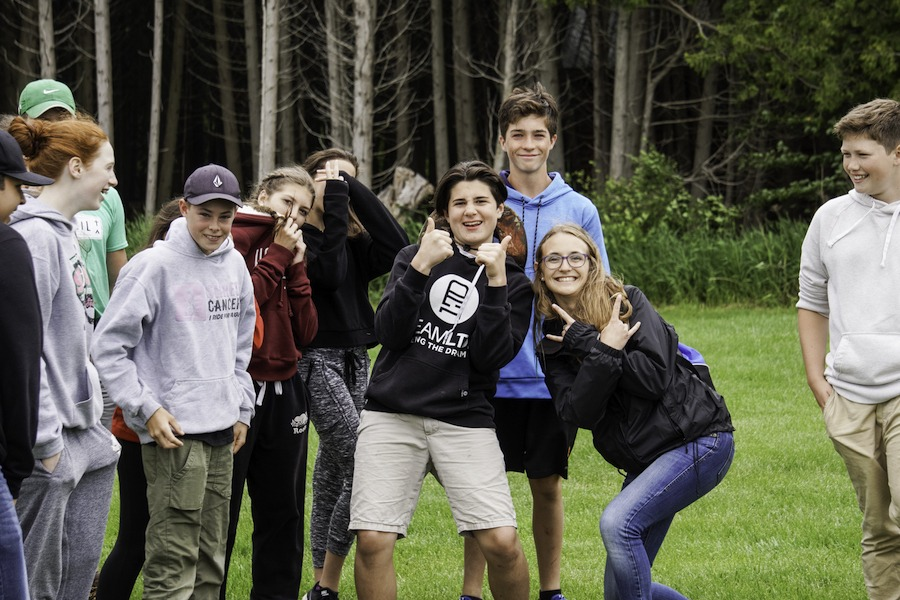 A staff member named Aqua strikes a funny rock and roll pose alongside a group of campers at summer camp.