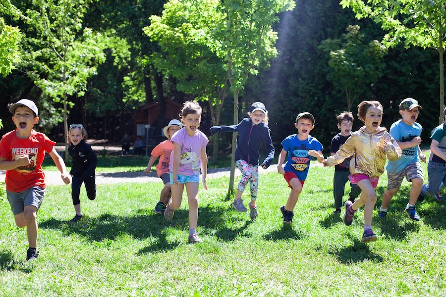 Ten campers are running, smiling, and screaming across a field at summer camp.