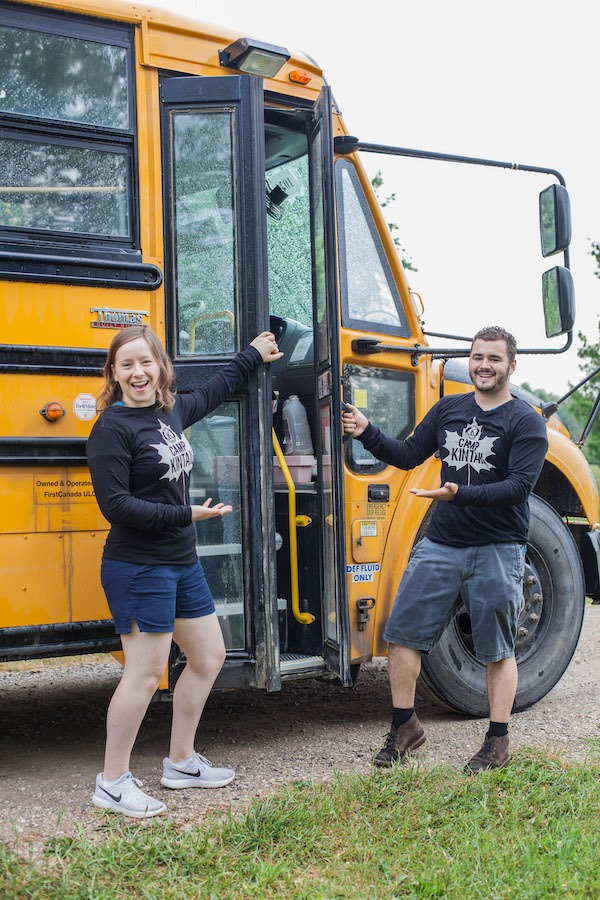 Camp Kintail staff members named Igneous and Stegosaurus hold open school bus doors performing a welcoming gesture to summer camp.