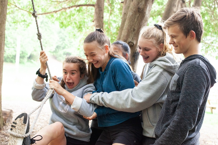 Four campers smile and hold onto one another catching the fifth camper who has swung over on a rope.